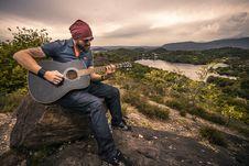 Free Man Playing Guitar On Hilltop Royalty Free Stock Photos - 83075288