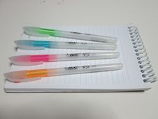 Free Bic Orange And White Ball Point Pens On Top Of Lined Paper Notebook Stock Photography - 83075472