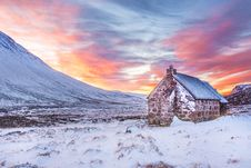 Free Brown House Surrounded By Snow Covered Field Near Snow Covered Mountain Under Yellow Blue And Orange Sunset Royalty Free Stock Photos - 83075728