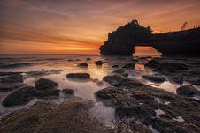 Free Orange And Yellow Sunset Skies Over Grey Seashore Rocks And Calmed Ocean Royalty Free Stock Image - 83076726