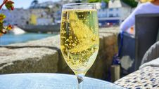Free Clear Champagne Glass With Yellow Liquid On Blue Glass Round Table Stock Photos - 83076973