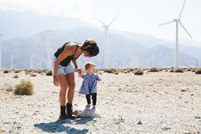 Free Woman Holding Her Child Walking Near Windmills Royalty Free Stock Image - 83077166