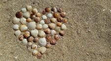 Free Heart Shape Sea Shells On Brown Beach Sand Royalty Free Stock Images - 83078649