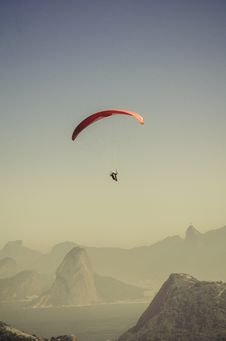 Free Person In Parachute Gliding Above Mountains Royalty Free Stock Images - 83078659