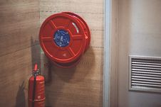 Free Red Fire Extinguisher Beside Hose Reel Inside The Room Royalty Free Stock Photography - 83079307