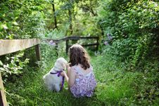 Free Girl And Puppy Sitting On Green Grass Surrounded With Shrubs During Daytime Royalty Free Stock Image - 83079616