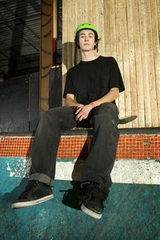 Skateboarder Sitting On His Board On Ramp Stock Photography