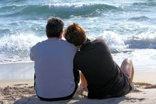 Free Couple Sitting On The Beach Royalty Free Stock Images - 8364509