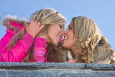 Girlfriends Blondes Kiss On Blue Sky Background Stock Photos