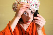 Girl Putting On Nail Varnish And Makeup Royalty Free Stock Image