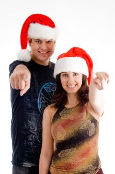 Pointing Couple Wearing Christmas Hat Stock Photography