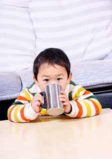 Boy Drinking Water Under Sofa Stock Photos
