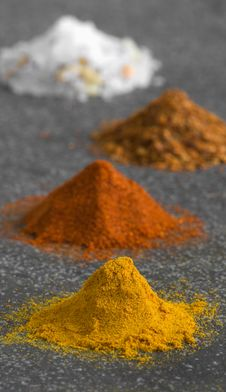 Four Piles Of Ground Spices On Grey Background Royalty Free Stock Images