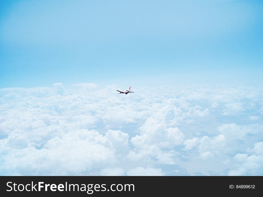 Airplane Flying Above Clouds