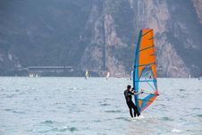 Free Man In Black Wetsuit Standing On Orange And Blue Sailboat During Daytime Stock Images - 84910594