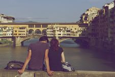 Free Couple Sitting Together Near Ponte Vecchio Stock Photo - 84925360