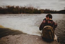 Free Man In Backpack Sitting By The Edge Of Rock Taking A Photo Of A Waterfall Royalty Free Stock Images - 84928749