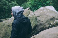 Free Man In Grey And Black Hooded Jacket Standing By Grey Rock Stock Photography - 84932272