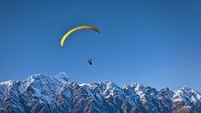 Free Person In Black Gliding Above Snow Covered Mountain Stock Images - 84932624
