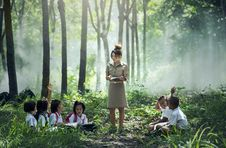 Free Woman In Gray Long Sleeve Dress Standing Between Childrens Near Woods And Grass Stock Images - 84933354