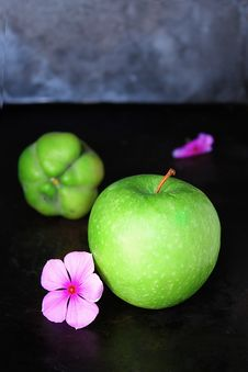 Free Green Apple Fruit Next To Purple Petaled Flower And Green Round Fruit On Black Table Stock Photos - 84935503