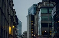 Free Dusk On A Street With Tall Buildings Royalty Free Stock Images - 84936069