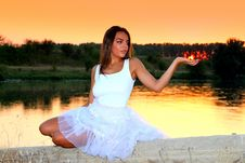 Free Woman In White Square Neckline Sleeveless Dress Sitting On Beige Wall Beside Body Of Water During Golden Time Royalty Free Stock Photos - 84936548