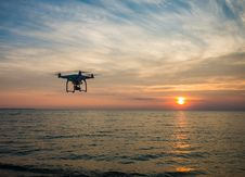 Free Black Quadcopter Drone Flying On The Sea Shore Under Blue And White Sky During Sun Set Stock Image - 84959181