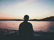 Free Silhouette Of A Person On A Dock Watching The Calm Ocean During Sunset Stock Image - 84965031