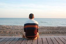 Free Man Sitting On Wooden Panel Facing In The Ocean Royalty Free Stock Images - 84969119