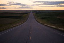 Free Green Field Between Empty Road Golden Hour Photo Royalty Free Stock Images - 84996169