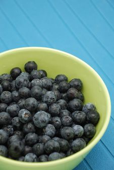 Blueberries In Green Bowl Over Blue Stock Images