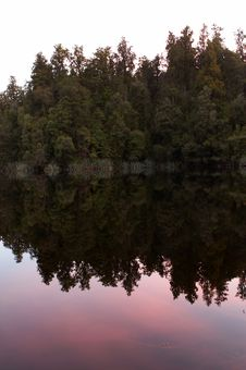 Reflection Of Trees On Lake At Sunset Stock Photos