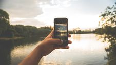 Free Close-up Of Hand Holding Mobile Phone Against Lake Royalty Free Stock Images - 85129009