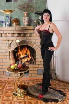 The Brunette And A Burning Fireplace. Royalty Free Stock Photography