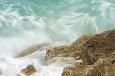 Green Waves Hitting Rocky Cliff Stock Photos