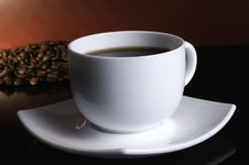 A White Cup Of Coffee And Coffee Beans Stock Images