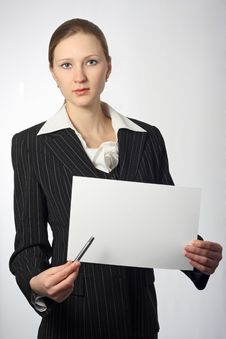 Young Beautiful Businesswoman With Sheet And Pen Royalty Free Stock Photography
