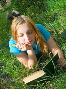 Free Girl Reads The Book Lying Down. Royalty Free Stock Photos - 866748