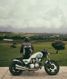 Free Person In Gray Hooded Jacket Leaning On White And Blue Cafe Racer With View Of Green Field Under White Clouds During Daytime Stock Photography - 86180952