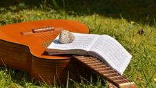 Free Song Book On Brown Classical Guitar On Green Grass During Daytime Royalty Free Stock Photos - 86183598