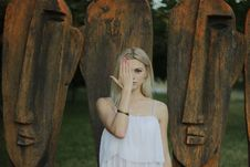 Free Woman Covering Face With Right Hand In Front Of Large Tribal Head Statue Royalty Free Stock Photos - 86220708