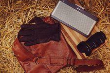 Free Brown Leather Gloves Beside Bose Speaker Dock And Black Dslr Camera Place On Red Leather Messenger Bag Stock Image - 86225261