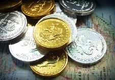 Free Gold And Silver Coins On World Map Stock Photography - 86227312