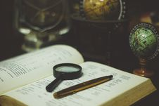Free Black Magnifying Glass Beside Gold Ball Point Pen On The Open Book Page Stock Photos - 86256003