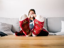 Free Girl On Couch Wearing Decorated Slippers Stock Images - 86258954