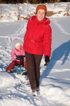 Free Mother Pulls Daughter On Snow Scooter Stock Photo - 8631520