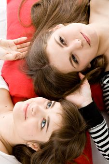 Two Girls Lying On Red Pillow Stock Photos