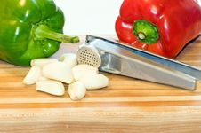 Peppers, Garlic Cloves And Press Royalty Free Stock Photos