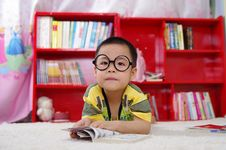 Free Boy Reading Book On Floor Stock Photos - 86312893